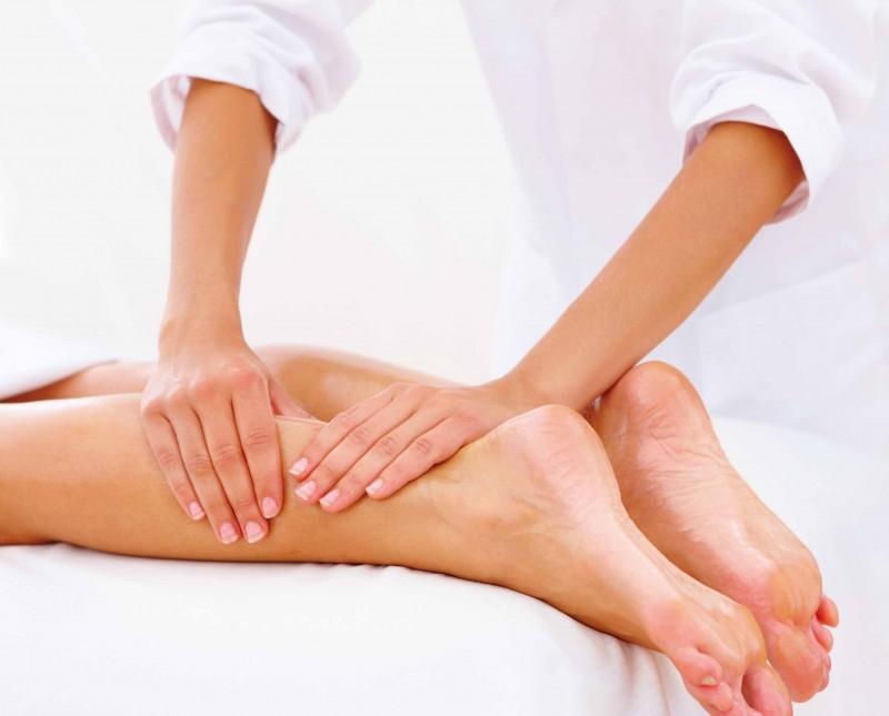 Closeup of legs receiving massage on white